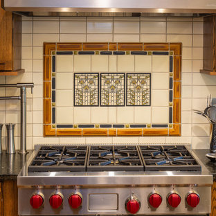 This is an example of a large classic u-shaped kitchen/diner in Other with a submerged sink, flat-panel cabinets, medium wood cabinets, granite worktops, white splashback, ceramic splashback, stainless steel appliances, light hardwood flooring, an island, brown floors and black worktops.