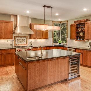 Idéer för stora amerikanska svart u-kök, med en undermonterad diskho, släta luckor, skåp i mellenmörkt trä, granitbänkskiva, vitt stänkskydd, stänkskydd i keramik, rostfria vitvaror, ljust trägolv, en köksö och brunt golv