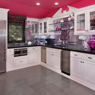 Example of an eclectic kitchen design in Orange County with glass-front cabinets, mirror backsplash and stainless steel appliances