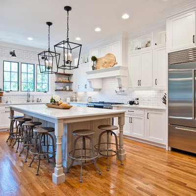 Example of a large cottage l-shaped medium tone wood floor and brown floor kitchen design in Nashville with white cabinets, quartz countertops, white backsplash, subway tile backsplash, stainless steel appliances, an island, white countertops and shaker cabinets
