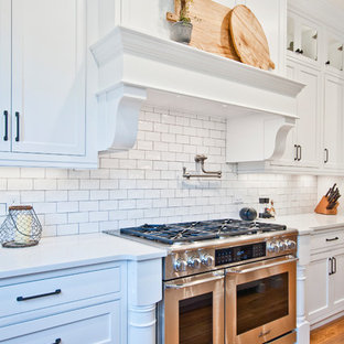 Large farmhouse open concept kitchen remodeling - Inspiration for a large farmhouse l-shaped medium tone wood floor and brown floor open concept kitchen remodel in Nashville with an undermount sink, recessed-panel cabinets, white cabinets, quartz countertops, white backsplash, subway tile backsplash, stainless steel appliances, an island and white countertops