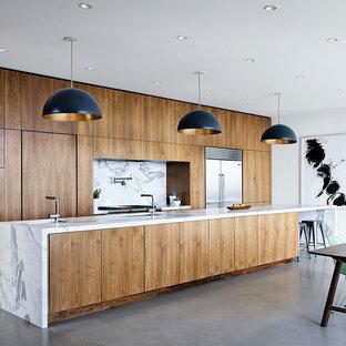 Réalisation d'une cuisine ouverte parallèle minimaliste avec un évier encastré, un placard à porte plane, des portes de placard en bois brun, un plan de travail en marbre, une crédence blanche, une crédence en dalle de pierre, un électroménager en acier inoxydable, béton au sol, un îlot central et un sol gris.