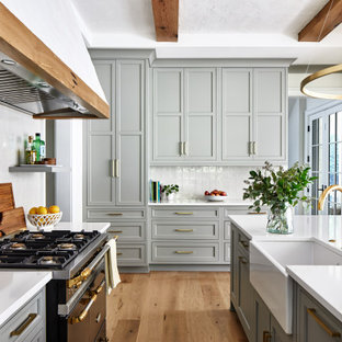 Design ideas for a large transitional l-shaped kitchen in DC Metro with a farmhouse sink, shaker cabinets, grey cabinets, quartz benchtops, white splashback, stone tile splashback, black appliances, with island, white benchtop, medium hardwood floors and brown floor.