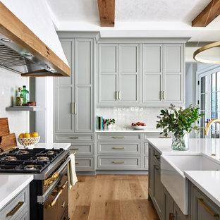 ワシントンD.C.の広いトランジショナルスタイルのおしゃれなキッチン (エプロンフロントシンク、シェーカースタイル扉のキャビネット、グレーのキャビネット、クオーツストーンカウンター、白いキッチンパネル、石タイルのキッチンパネル、黒い調理設備、白いキッチンカウンター、無垢フローリング、茶色い床) の写真