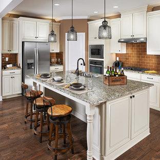 Пример оригинального дизайна: кухня в классическом стиле с двойной раковиной, фасадами с выступающей филенкой, белыми фасадами, оранжевым фартуком, фартуком из плитки кабанчик и техникой из нержавеющей стали