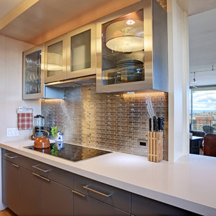 This is an example of a mid-sized contemporary galley separate kitchen in San Francisco with an undermount sink, flat-panel cabinets, beige cabinets, solid surface benchtops, metallic splashback, metal splashback, panelled appliances, medium hardwood floors, a peninsula and yellow floor.