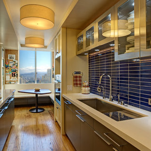 Photo of a small contemporary galley eat-in kitchen in San Francisco with an undermount sink, glass-front cabinets, stainless steel cabinets, solid surface benchtops, blue splashback, ceramic splashback, stainless steel appliances, medium hardwood floors, a peninsula and yellow floor.