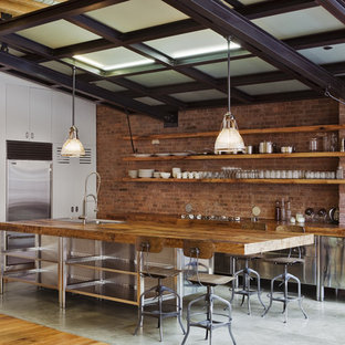 Inspiration for a mid-sized industrial l-shaped eat-in kitchen in New York with stainless steel appliances, stainless steel cabinets, wood benchtops, flat-panel cabinets, red splashback, brick splashback, with island, a farmhouse sink, concrete floors and grey floor.