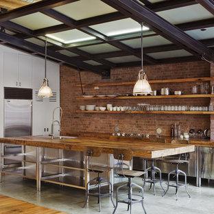 Exemple d'une cuisine américaine industrielle en L de taille moyenne avec un électroménager en acier inoxydable, une façade en inox, un plan de travail en bois, un placard à porte plane, une crédence rouge, une crédence en brique, un îlot central, un évier de ferme, béton au sol et un sol gris.