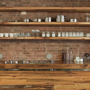 Mid-sized urban l-shaped concrete floor eat-in kitchen photo in New York with wood countertops, a farmhouse sink, flat-panel cabinets, stainless steel cabinets, red backsplash, brick backsplash, stainless steel appliances and an island