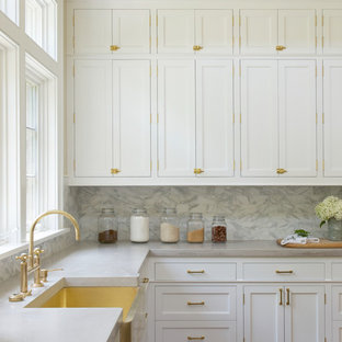 Inspiration for a transitional open plan kitchen in New York with a farmhouse sink, shaker cabinets, white cabinets, white splashback, medium hardwood floors, marble benchtops, with island and marble splashback.