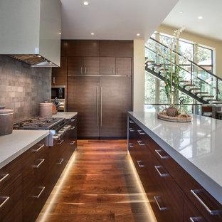 Große Moderne Küche mit flächenbündigen Schrankfronten, dunklen Holzschränken, Quarzit-Arbeitsplatte, Küchenrückwand in Grau, Rückwand aus Steinfliesen, Elektrogeräten mit Frontblende, dunklem Holzboden und Kücheninsel in Salt Lake City