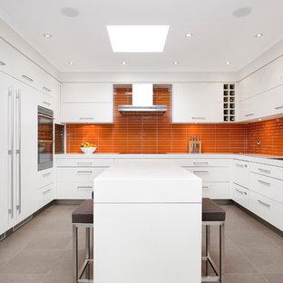 Foto de cocina en U, contemporánea, con fregadero de doble seno, salpicadero naranja, electrodomésticos con paneles, suelo de baldosas de porcelana y una isla