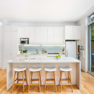 This is an example of a transitional single-wall kitchen in Sydney with an undermount sink, flat-panel cabinets, white cabinets, granite benchtops, green splashback, glass sheet splashback, stainless steel appliances, medium hardwood floors, with island, brown floor and white benchtop.