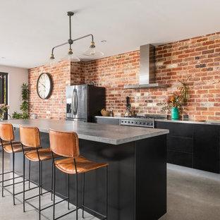 Industriell inredning av ett mellanstort grå grått kök, med betonggolv, en integrerad diskho, släta luckor, svarta skåp, bänkskiva i betong, rött stänkskydd, stänkskydd i tegel, rostfria vitvaror, en köksö och grått golv