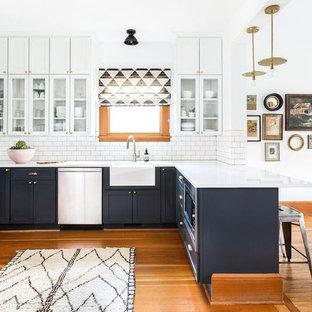Inspiration för mellanstora lantliga kök, med en rustik diskho, skåp i shakerstil, grå skåp, vitt stänkskydd, stänkskydd i tunnelbanekakel, rostfria vitvaror, mellanmörkt trägolv, en halv köksö, bänkskiva i kvartsit och brunt golv