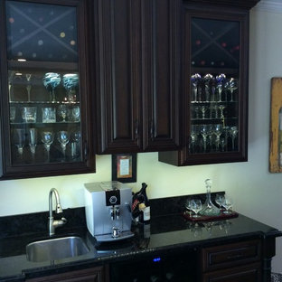 This is an example of a small classic galley kitchen pantry in San Francisco with a submerged sink, raised-panel cabinets, dark wood cabinets, granite worktops, black splashback, stone slab splashback, black appliances and dark hardwood flooring.