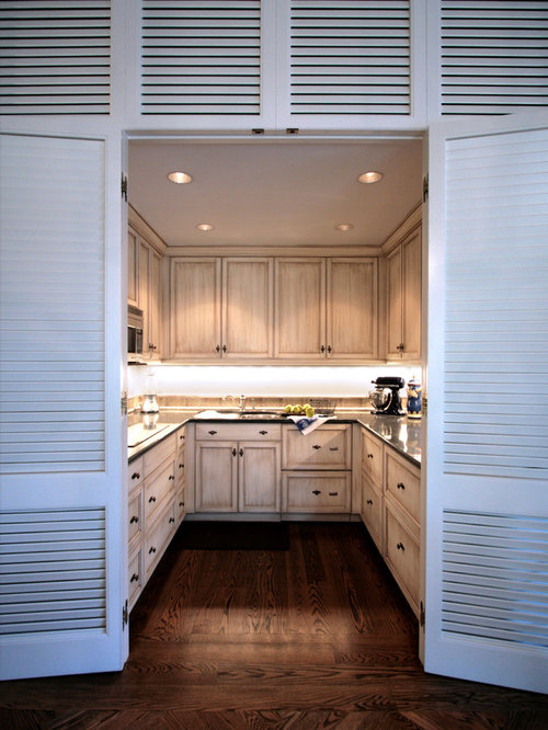 awesome spice kitchen design #2: Example of an island style u-shaped enclosed kitchen design in Charleston  with distressed cabinets