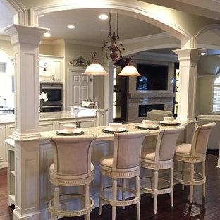 Immagine di un'ampia cucina vittoriana con lavello sottopiano, ante con bugna sagomata, ante bianche, top in granito, paraspruzzi bianco, elettrodomestici in acciaio inossidabile e 2 o più isole