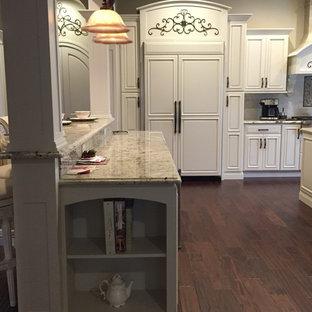 他の地域の巨大なヴィクトリアン調のおしゃれなキッチン (アンダーカウンターシンク、レイズドパネル扉のキャビネット、白いキャビネット、御影石カウンター、白いキッチンパネル、シルバーの調理設備) の写真