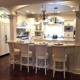 Geräumige Klassische Küche in U-Form mit Vorratsschrank, Unterbauwaschbecken, profilierten Schrankfronten, weißen Schränken, Granit-Arbeitsplatte, Küchenrückwand in Weiß, Küchengeräten aus Edelstahl und zwei Kücheninseln in Sonstige