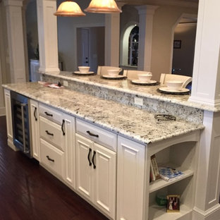 This is an example of an expansive victorian u-shaped kitchen pantry in Other with an undermount sink, raised-panel cabinets, white cabinets, granite benchtops, white splashback, stainless steel appliances and multiple islands.