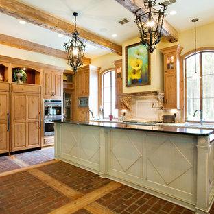 Foto di una cucina con ante con bugna sagomata, ante in legno scuro, paraspruzzi beige, paraspruzzi con piastrelle in pietra, elettrodomestici da incasso, lavello sottopiano, top in granito e pavimento in mattoni