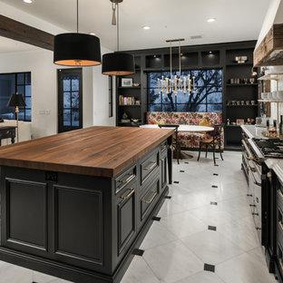 フェニックスの巨大なカントリー風おしゃれなキッチン (ドロップインシンク、レイズドパネル扉のキャビネット、黒いキャビネット、大理石カウンター、マルチカラーのキッチンパネル、大理石の床、パネルと同色の調理設備、大理石の床、マルチカラーの床、マルチカラーのキッチンカウンター) の写真