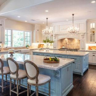 Inredning av ett mycket stort beige beige l-kök, med en rustik diskho, rostfria vitvaror, mörkt trägolv, flera köksöar, brunt golv, luckor med profilerade fronter, vita skåp, granitbänkskiva, beige stänkskydd och stänkskydd i stenkakel