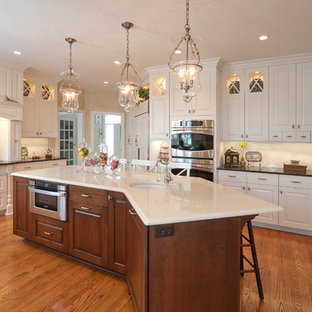 Elegant u-shaped eat-in kitchen photo in New York with an undermount sink, raised-panel cabinets, white cabinets, granite countertops, white backsplash, glass sheet backsplash and stainless steel appliances