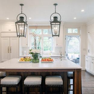 ミルウォーキーの広いトラディショナルスタイルのおしゃれなキッチン (エプロンフロントシンク、落し込みパネル扉のキャビネット、白いキャビネット、クオーツストーンカウンター、白いキッチンパネル、サブウェイタイルのキッチンパネル、パネルと同色の調理設備、白いキッチンカウンター、茶色い床、無垢フローリング) の写真