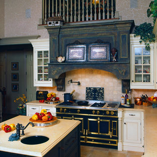 Large traditional l-shaped eat-in kitchen in Other with a farmhouse sink, beaded inset cabinets, white cabinets, limestone benchtops, beige splashback, ceramic splashback, black appliances, porcelain floors and multiple islands.