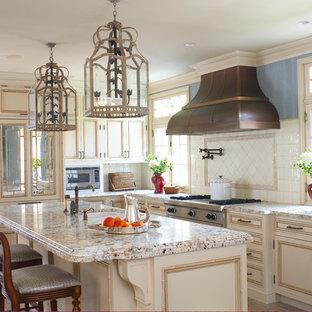 Idéer för ett kök, med en dubbel diskho, luckor med infälld panel, beige skåp, granitbänkskiva, vitt stänkskydd, stänkskydd i keramik, rostfria vitvaror, kalkstensgolv och en köksö