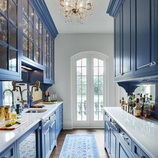 Idee per una cucina di medie dimensioni con lavello sottopiano, ante con bugna sagomata, ante blu, top in quarzite, paraspruzzi a specchio, elettrodomestici da incasso, parquet scuro, nessuna isola, pavimento marrone e top bianco