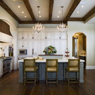 Klassisk inredning av ett kök, med luckor med upphöjd panel, beige skåp, mörkt trägolv, en köksö och rostfria vitvaror