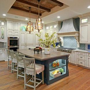 Cette photo montre une cuisine en L avec un évier de ferme, un placard avec porte à panneau surélevé, des portes de placard beiges, une crédence bleue, une crédence en carreau de verre, un électroménager en acier inoxydable, un sol en bois brun, un îlot central, un sol marron et un plan de travail beige.