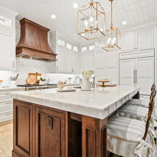 Foto på ett mellanstort vintage vit kök, med en undermonterad diskho, luckor med profilerade fronter, vita skåp, bänkskiva i kvartsit, vitt stänkskydd, stänkskydd i marmor, integrerade vitvaror, kalkstensgolv, en köksö och beiget golv