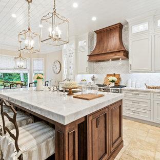 Bild på ett mellanstort vit vitt kök, med en undermonterad diskho, luckor med profilerade fronter, vita skåp, bänkskiva i kvartsit, vitt stänkskydd, stänkskydd i marmor, integrerade vitvaror, kalkstensgolv, en köksö och beiget golv