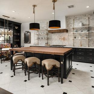 フェニックスの巨大な地中海スタイルのおしゃれなキッチン (アンダーカウンターシンク、落し込みパネル扉のキャビネット、黒いキャビネット、木材カウンター、マルチカラーのキッチンパネル、大理石の床、パネルと同色の調理設備、大理石の床、マルチカラーの床、マルチカラーのキッチンカウンター) の写真