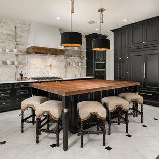 Foto på ett medelhavsstil kök, med luckor med infälld panel, svarta skåp, flerfärgad stänkskydd, integrerade vitvaror, en köksö, flerfärgat golv och träbänkskiva