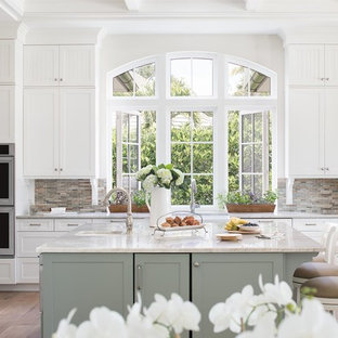 Photo of a traditional eat-in kitchen in Miami with a farmhouse sink, shaker cabinets, green cabinets, multi-coloured splashback, matchstick tile splashback, stainless steel appliances, medium hardwood floors, with island, beige floor and beige benchtop.