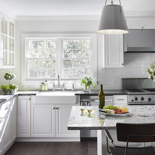 Inspiration for a medium sized classic u-shaped kitchen/diner in Minneapolis with a belfast sink, white cabinets, dark hardwood flooring, an island, raised-panel cabinets, granite worktops, white splashback, ceramic splashback, stainless steel appliances and brown floors.
