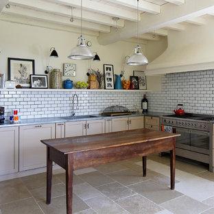 Inredning av ett lantligt avskilt, stort l-kök, med en integrerad diskho, luckor med infälld panel, beige skåp, vitt stänkskydd, stänkskydd i tunnelbanekakel, integrerade vitvaror och en köksö