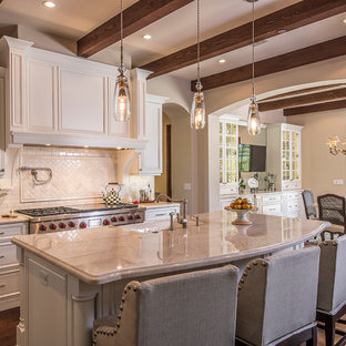 Example of a mid-sized french country galley dark wood floor and brown floor eat-in kitchen design in Phoenix with a farmhouse sink, raised-panel cabinets, white cabinets, white backsplash, stainless steel appliances, an island and ceramic backsplash