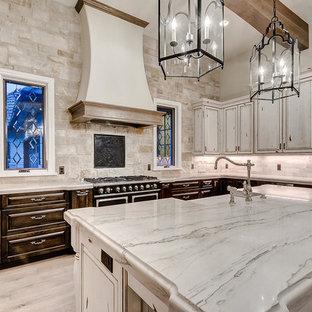 Exemple d'une grand cuisine ouverte en U avec un évier de ferme, un placard avec porte à panneau surélevé, des portes de placard en bois vieilli, un plan de travail en marbre, une crédence blanche, une crédence en carrelage de pierre, un électroménager en acier inoxydable, un sol en bois clair, un îlot central, un sol marron et un plan de travail blanc.