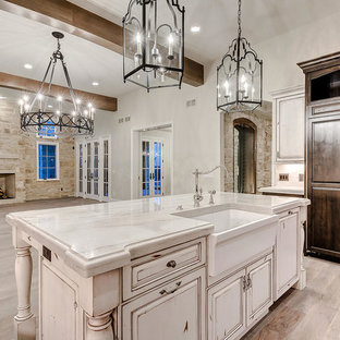 Large french country open concept kitchen photos - Inspiration for a large french country u-shaped light wood floor and brown floor open concept kitchen remodel in Denver with a farmhouse sink, raised-panel cabinets, distressed cabinets, marble countertops, white backsplash, stone tile backsplash, stainless steel appliances, an island and white countertops