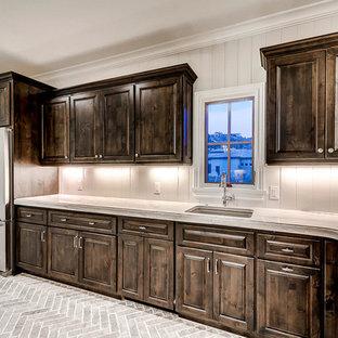Inspiration för stora beige kök, med en undermonterad diskho, luckor med upphöjd panel, skåp i mörkt trä, marmorbänkskiva, vitt stänkskydd, stänkskydd i trä, rostfria vitvaror, tegelgolv och grått golv