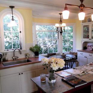 ポートランドの中サイズの地中海スタイルのおしゃれなキッチン (アンダーカウンターシンク、シェーカースタイル扉のキャビネット、白いキャビネット、タイルカウンター、ベージュキッチンパネル、セラミックタイルのキッチンパネル、シルバーの調理設備の) の写真