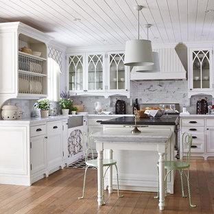 Shabby chic-inspirerad inredning av ett mellanstort kök, med en rustik diskho, luckor med infälld panel, vita skåp, grått stänkskydd, rostfria vitvaror, mellanmörkt trägolv, en köksö, brunt golv och stänkskydd i marmor