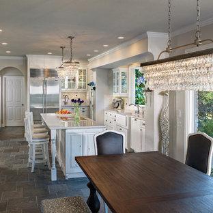 Inredning av ett klassiskt stort kök, med en rustik diskho, skåp i shakerstil, vita skåp, bänkskiva i kvarts, vitt stänkskydd, stänkskydd i tunnelbanekakel, rostfria vitvaror, skiffergolv och en köksö